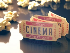 A strip of cinema tickets is strewn amongst some popcorn.